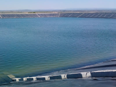 Black HDPE geomembrane is laid around the pond, several stones are pressed on its edges.