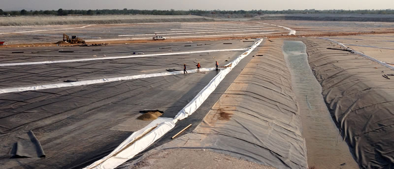 Black HDPE geomembrane is laid in a large area, several machines and workers are working on it.