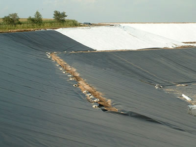 White and black HDPE geomembrane applied in slope, and there are three workers working on it.