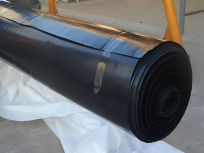 Two workers are packaging a roll of black HDPE geomembrane with white woven bags.