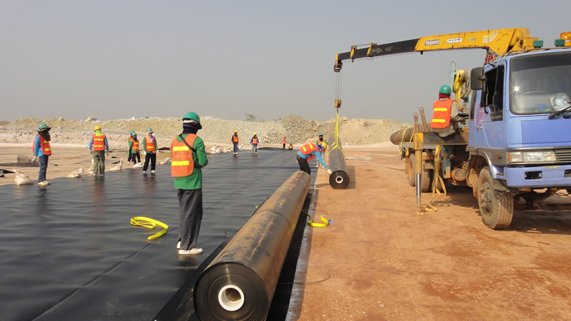 A heavy crane is putting the black HDPE geomembrane roll on the ground, and two workers hold one side of the HDPE geomembrane, other workers are waiting.