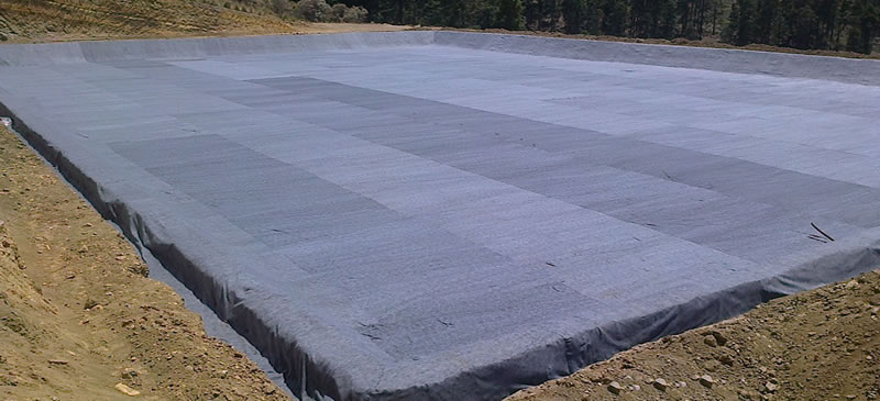 A piece of huge rectangle shaped area is laid by long fiber geotextile fabric, and there is woods beside it.