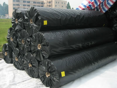 Nine long fiber geotextile fabric rolls with black plastic film are lying on a piece of white fabric, and more packaged rolls are behind them.