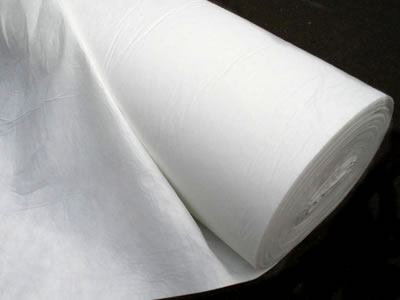 A roll of long fiber geotextile fabric is lying on the black background.