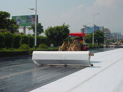 Two workers are operating the machine to lay white long fiber geotextile fabric on the road bed.