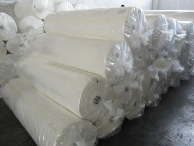 Some packaged white long fiber geotextile fabric rolls are lying on the ground in the factory.