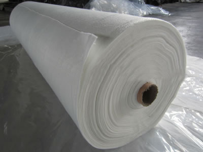 A roll of white long fiber geotextile fabric is put on the transparent plastic film.