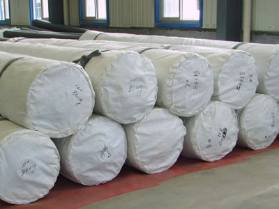 Twelve rolls of HDPE geomembrane packaged with white woven bags are lying on the ground in the factory.