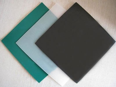 There are three pieces of HDPE geomembrane sample in green, white and black color, and they are lying on the ground.