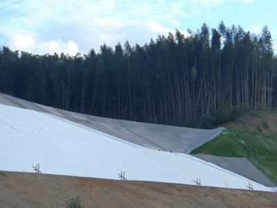 White HDPE geomembrane is put on the slope, and there are grasslands and woods beside it.