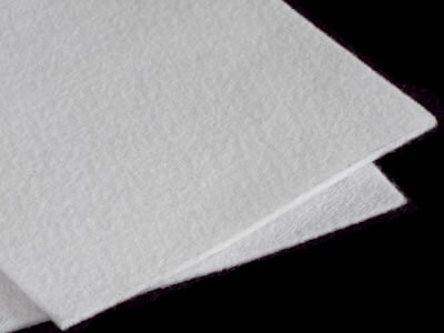 Two pieces of white long fiber geotextile fabric sample are lying on the black background.